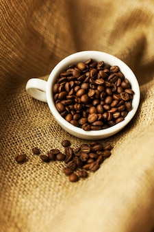 A scattering of coffee beans with a cup of coffee.