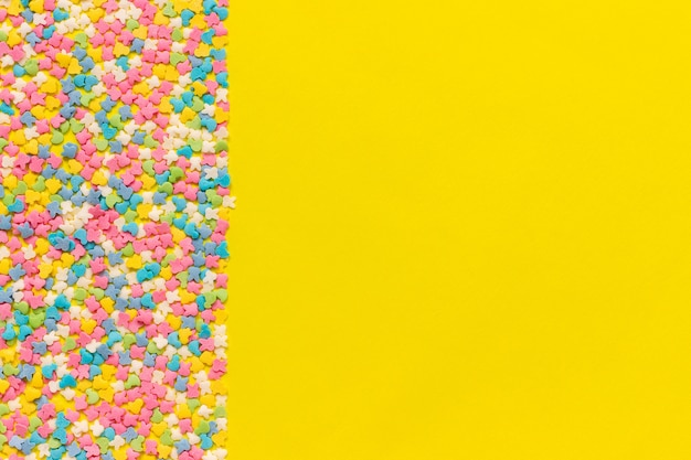Scattering multicolored confectionery topping dressing on yellow paper. festive background.