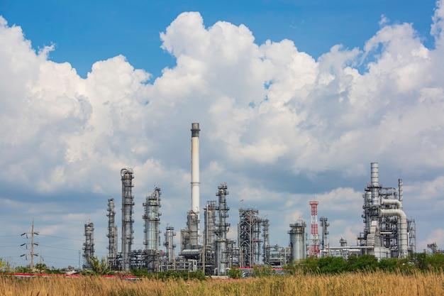 석유화학 산업 푸른 하늘과 잔디의 탱크 정유 공장 타워와 기둥 탱크 오일의 장면 오후