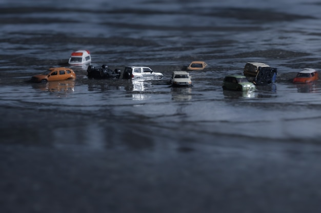 Scene of cars (miniature, toy model ) in flood from natural disasters,heavy rain, typhoon, hurricane.transportation,car insurance concept