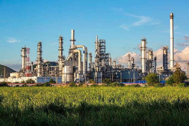 Вечер сцены танка нефтеперерабатывающий завод башни и колонны танка нефти нефтехимической промышленности голубое небо и лужайка