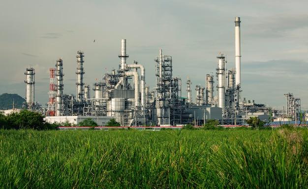 Вечер сцены танкового нефтеперерабатывающего завода башни и колонны танка нефти газона нефтехимической промышленности