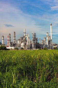 석유화학 산업 앞 잔디밭의 탱크 정유 공장 타워와 기둥 탱크 오일의 장면 저녁