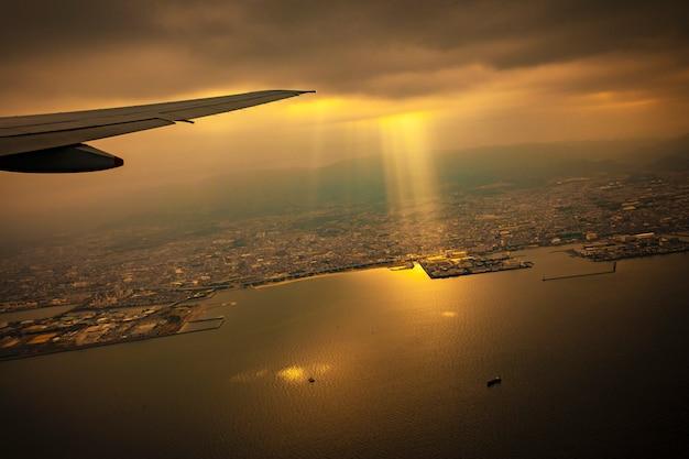 Scene from plane window of sun light ray through rain cloud over osaka town japan