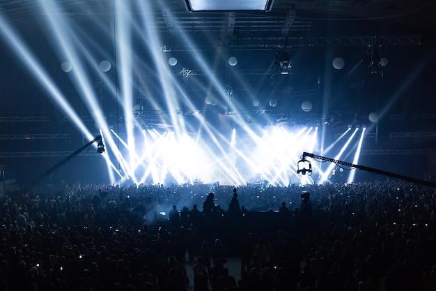 Сцена освещена красивыми лучами осветительного оборудования. концертная толпа веселится в центре большого зала.