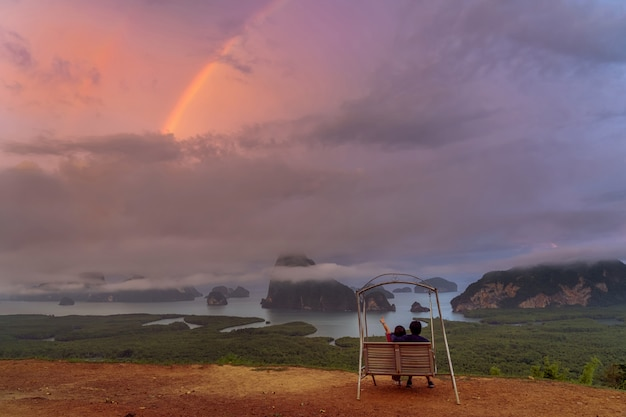 Scene of lovers sitting and pointing to the rainbow over the fantastic landscape of samed
