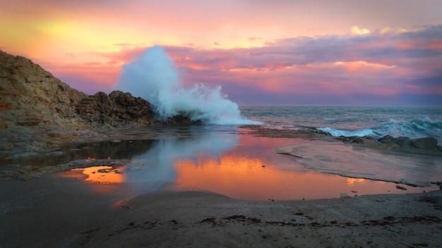 秋の日没の砕波のシーン