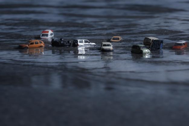 自然災害、大雨、台風、ハリケーンによる洪水の車(ミニチュア、トイモデル)のシーン。輸送、自動車保険の概念