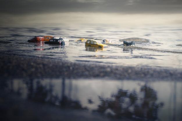 Сцена автомобилей (миниатюра, игрушечная модель) в наводнении от стихийных бедствий, сильного дождя, тайфуна, урагана. транспорт, концепция страхования автомобилей