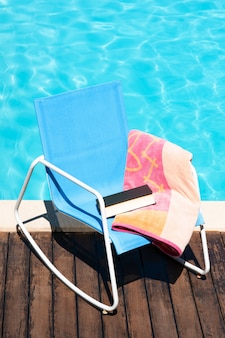 Scene of sun chair with beach towel and book on swimming pool