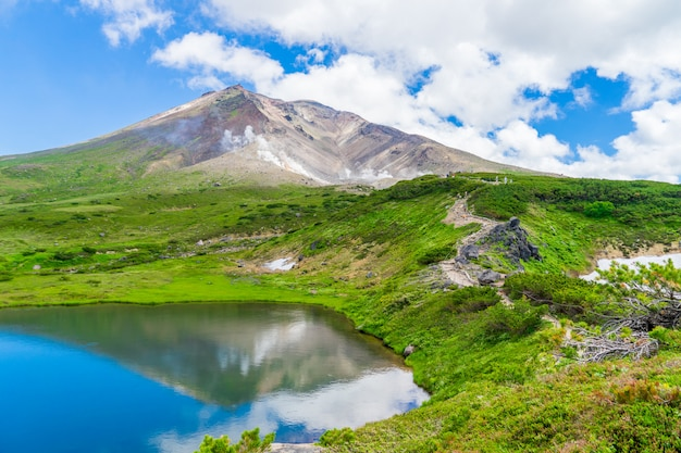 Scenery of asahidake peak mountain with reflection water and blue cloudy sky in summer, asahikawa, hokkaido, japan.
