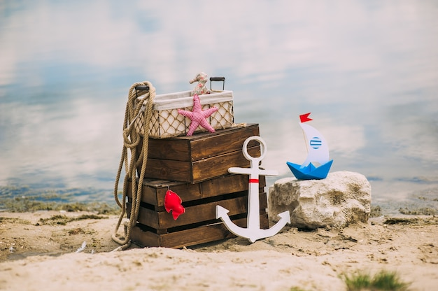 Scenery and details in a nautical style on the sandy beach. marine themes. wooden boxes, anchor, boat, factory parts and sea rope