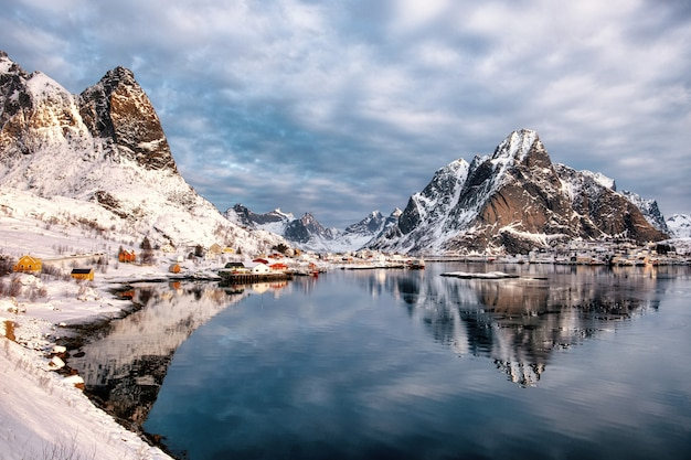 Scenery of fishing village of reine with mountains reflection on coastline in winter at lofoten islands