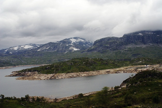 Scenery of a landscape with a lake surrounded by green mountains under a cloudy sky in norway
