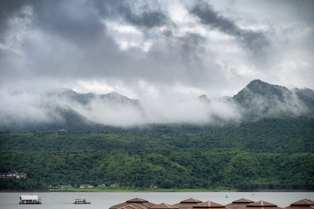Scenery of mountain with foggy and boat sailing on dam in rainy season