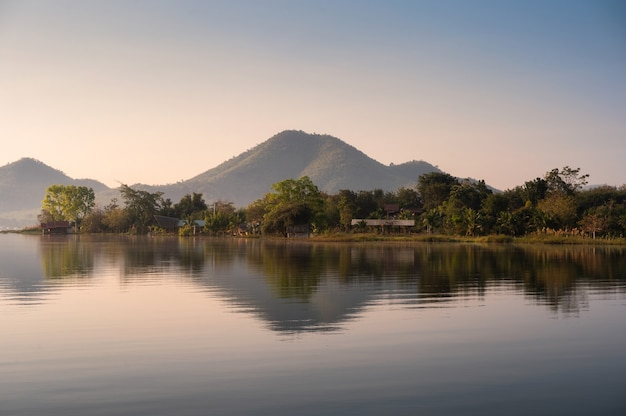 Scenery of mountain with traditional village floating on lam taphoen reservoir in the morning at suphanburi