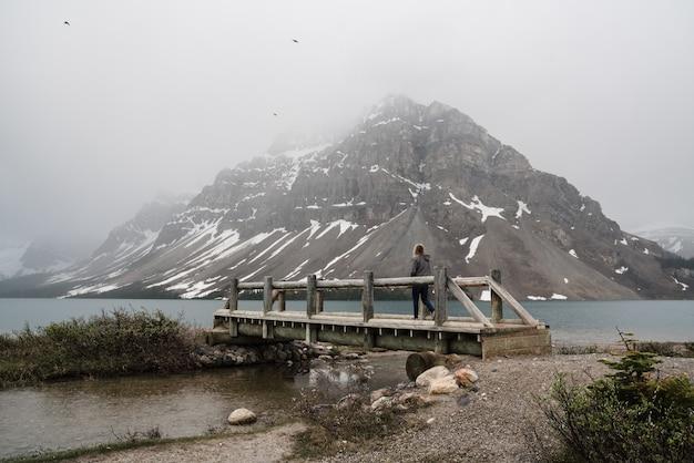 Пейзаж человека, стоящего на пирсе, ведущем к реке у скального образования