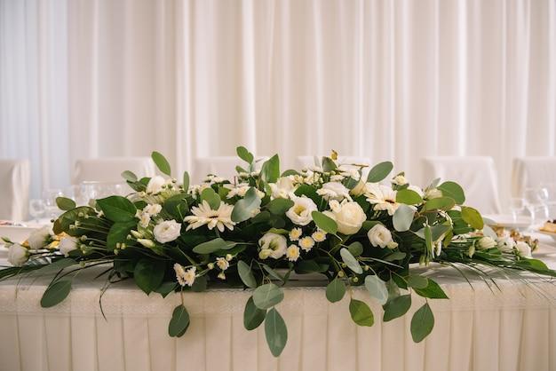 レストランのお祝いのテーブルに生花の風景