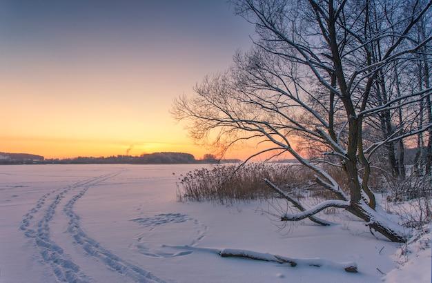 Пейзаж озера, покрытого льдом зимой, со следами людей на снегу на закате