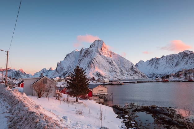 겨울에 lofoten 섬의 풍경입니다. 스칸디나비아, 노르웨이의 해안선에 어촌 마을이있는 눈 덮인 산