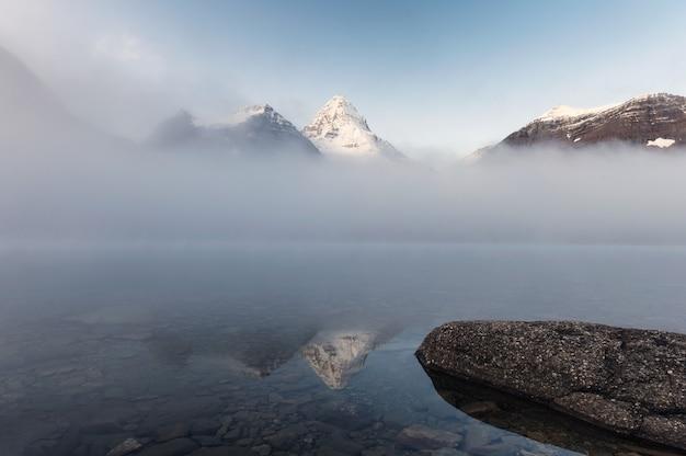 Пейзаж горы ассинибойн в тумане на озере магог утром в провинциальном парке, альберта, канада