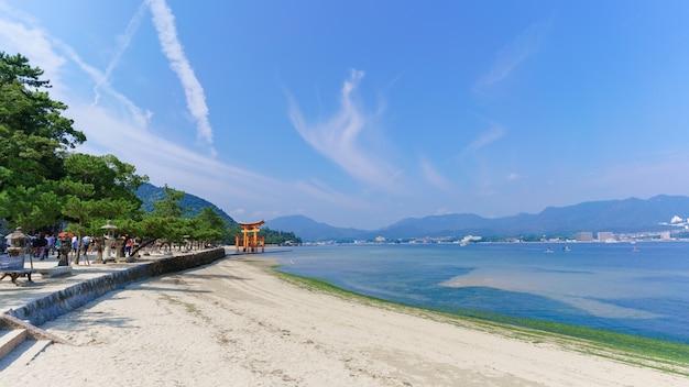 만에 있는 이쓰쿠시마 신사의 유명한 오렌지색 떠 있는 일본 신사(도리이)를 바라보는 미야지마 섬의 바다 해안 풍경