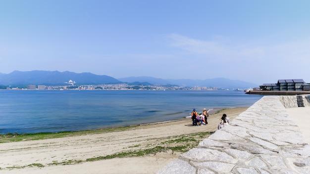사람들이 해변에서 많은 활동을 할 수 있는 미야지마 섬의 바다 해안 풍경, 일본 히로시마