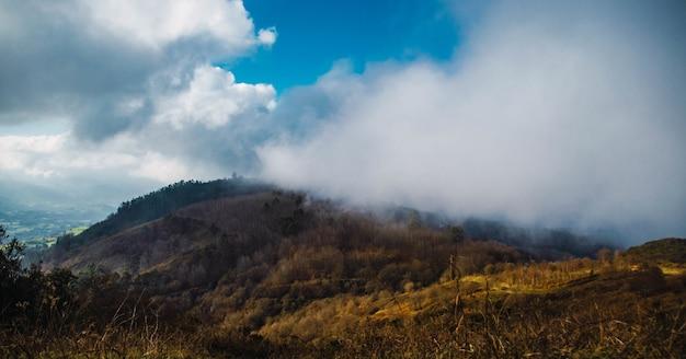 Пейзаж дыма над горой под облачным небом