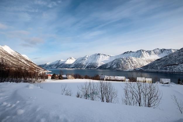 ノルウェーのセンジャ島の冬の海岸線の雪の山脈とノルウェーの村の風景