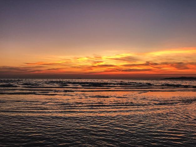 Пейзаж заката на пляже с успокаивающими волнами океана
