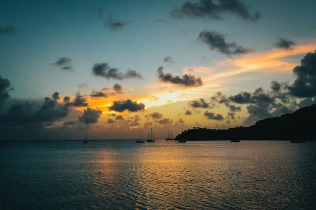 Пейзаж заката с силуэтом горы и лодки в море