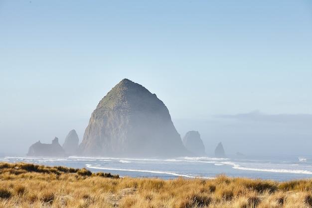 Пейзаж скалы стог сена в утреннем тумане на пляже кэннон, штат орегон