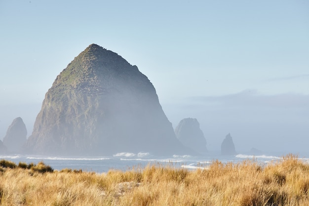 오레곤 캐논 비치에서 아침 안개에 건초 더미 바위의 풍경