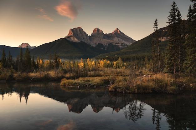 カナダの朝の秋の森に映るスリーシスターズマウンテンの風景