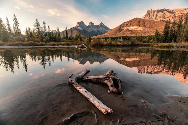 スリー シスターズ山脈の風景は、カナダ、キャンモアの秋の森で弓の川を反射します