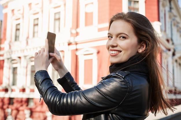 町の景色は素晴らしいです。外国の都市での遠足で写真を撮る魅力的な女性の肖像画