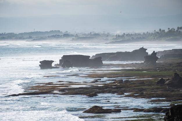 Пейзаж волны, ударяющей по скалам на береговой линии на бали, индонезия