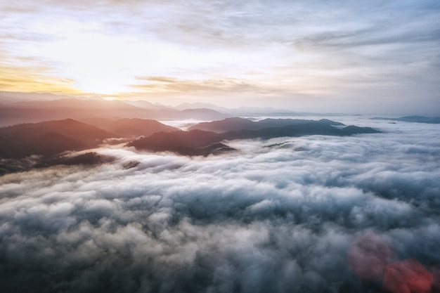 The scenery on the summit, mountain silhouette above the clouds at sunrise.