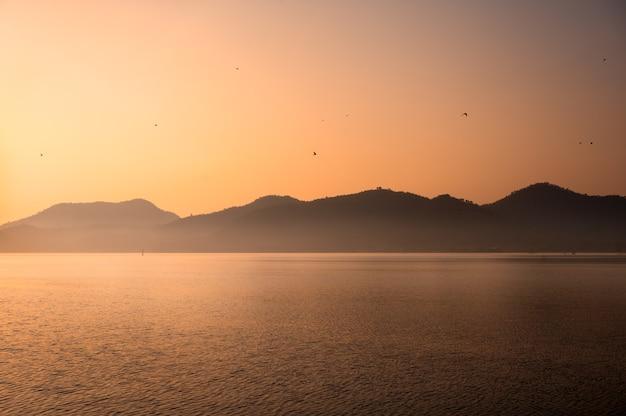 Scenery of sunrise on mountain range with fog and birds flying