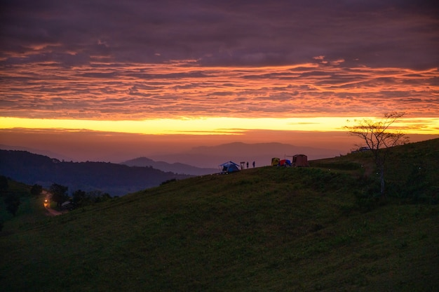 Scenery of sunrise over mountain with tent camping on hill in countryside at morning