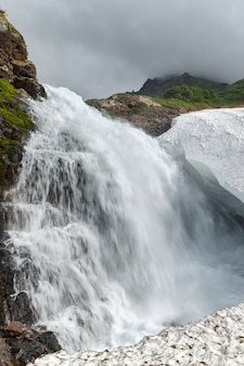 Пейзажный вид на идиллический каскадный водопад, падающий в снежное поле на скалистой горе