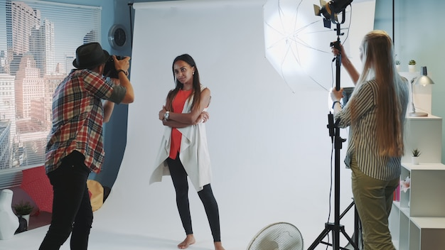Behind the scenes on photo shoot: photographer asking assistant to direct the lighting to the model