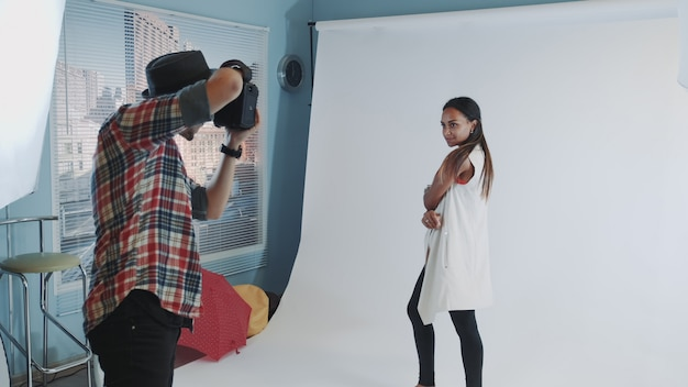 Behind the scenes on photo shoot: professional photographer working in studio by taking photos of black model