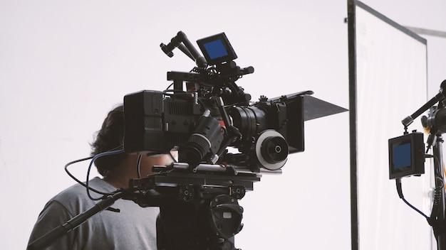 Behind the scenes of video camera shooting by film crew team production people in big studio