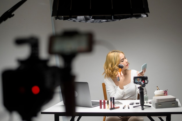 Behind the scenes young blonde woman entrepreneur working with laptop presents cosmetic products during online live stream on white