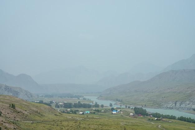 霧の中の山川沿いの山村のある風光明媚な高山の風景。川岸の田園地帯と大気の霧の風景。雨天時の川沿いの山村の美しい景色。