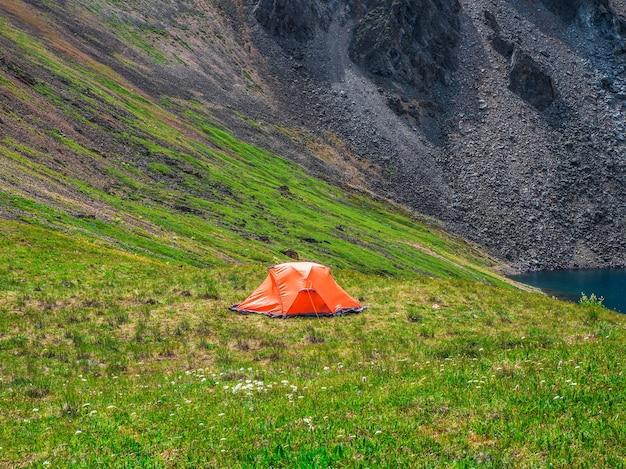美しい緑の山の高原の谷の近くにオレンジ色のテントのある風光明媚な高山の風景。オレンジ色のテントと日当たりの良い高山の風景。旅行のコンセプト。