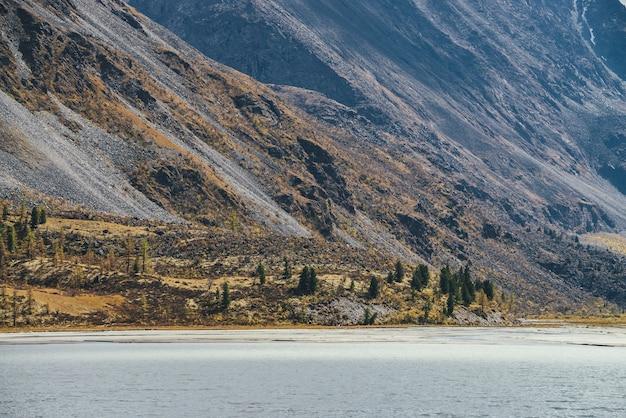 針葉樹と湖の上の日差しの中で岩と高山の風光明媚な秋の風景。日光の下で秋の色の丘の中腹に森を望む山の湖の美しい風景。