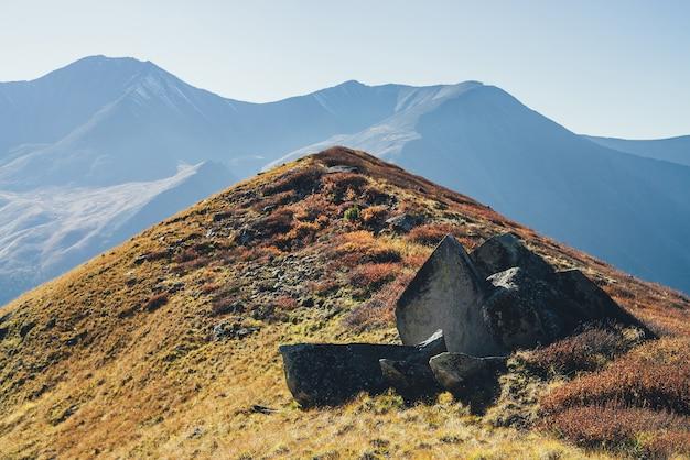 日光の下で山のシルエットの背景に赤い丘の上の鋭い粉々に砕けた石と風光明媚な秋の風景。秋の色の丘とカラフルな山の風景。素晴らしい秋の高山の景色。