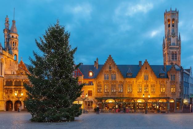 ベルギー、ブルージュの美しい夜の中世のクリスマスブルク広場のある風光明媚な街並み